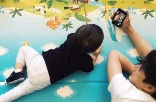 靳东趴地上和孩子玩手机,一家人幸福美满